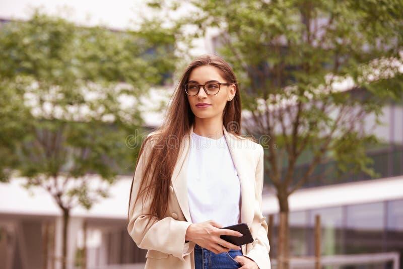 有她的手机的年轻女实业家走在街道上的在城市 库存图片