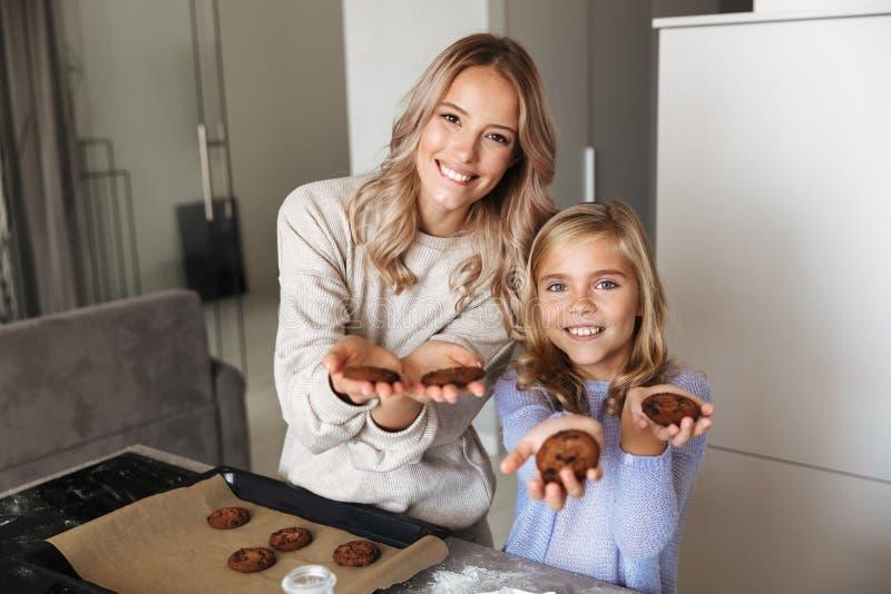 有她的拿着曲奇饼的在家户内妹厨房的年轻女人 库存照片