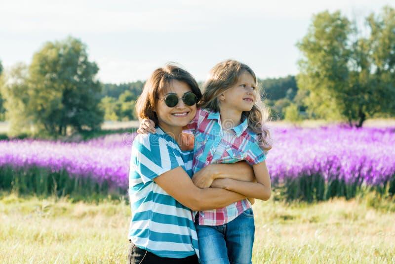 有她的接受走在自然,背景晴朗的夏日紫色淡紫色领域的一点女儿的微笑的母亲 库存图片