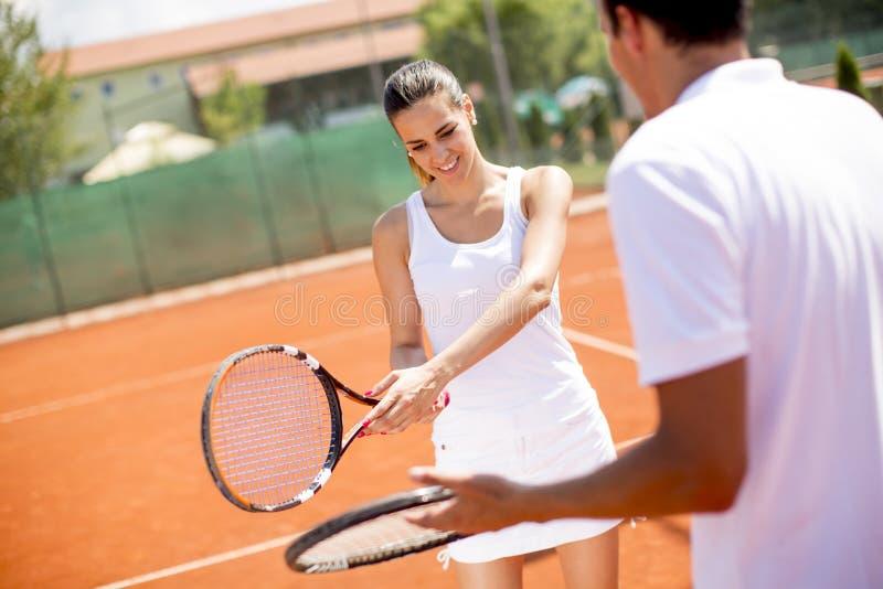 有她的教练员实践的服务的俏丽的年轻女人在室外网球场 免版税图库摄影