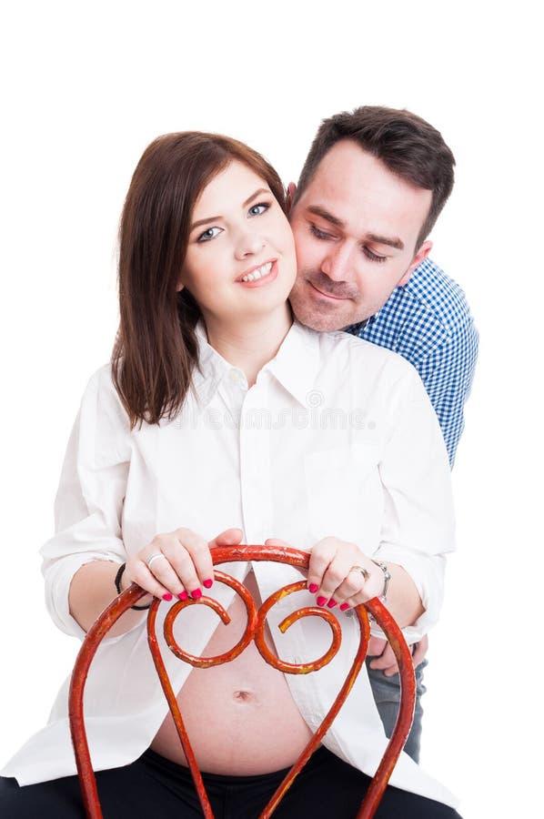 有她的显示喜爱的丈夫的可爱的年轻孕妇 免版税图库摄影
