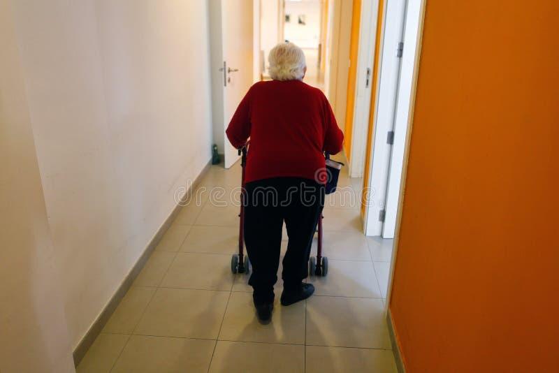 有她的步行者的资深妇女在她的老人院里面走廊在马略卡 免版税库存照片