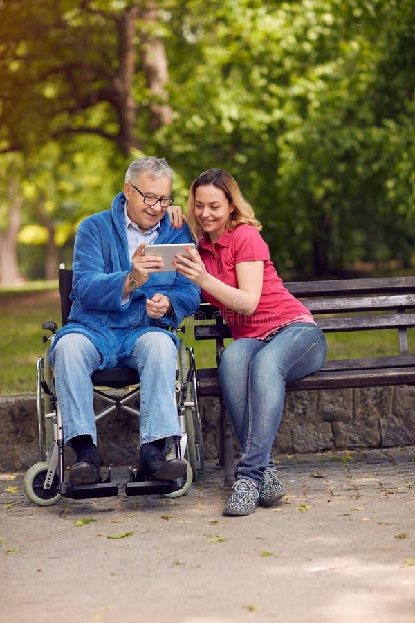 有她的残疾父亲的女儿使用数字式轮椅的 库存图片