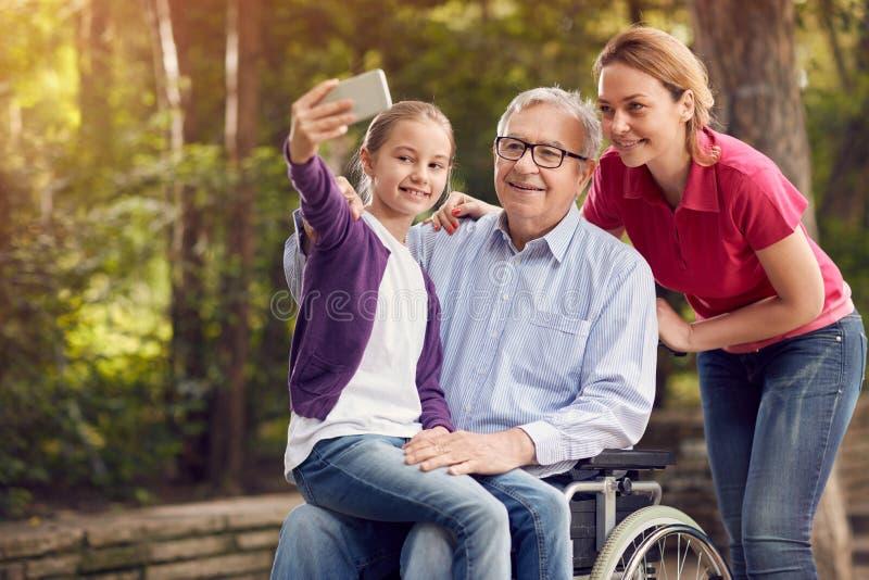 有她的残疾父亲的女儿轮椅和granddaughte的 库存图片