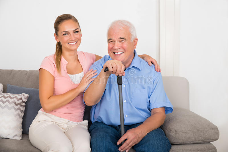有她的残疾父亲的妇女坐沙发 图库摄影