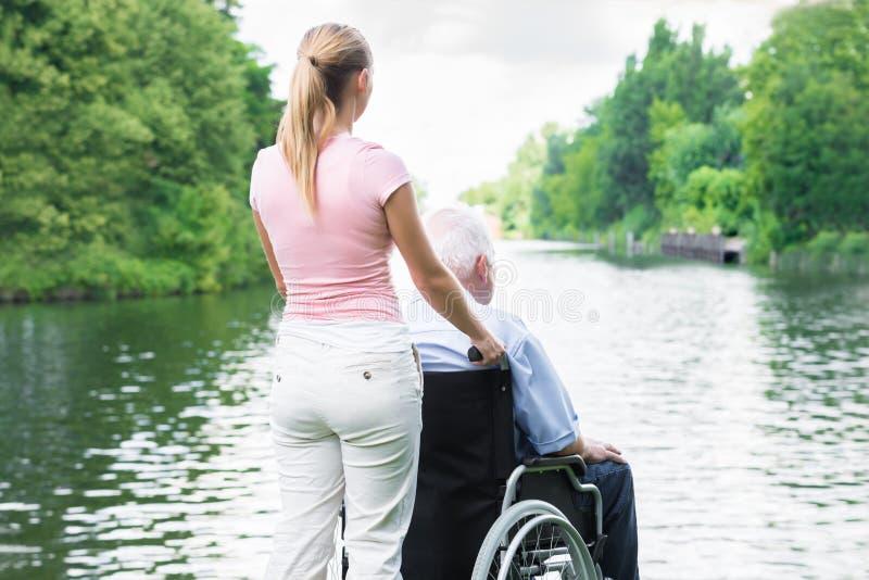 有她的残疾父亲的妇女看湖的轮椅的 免版税图库摄影