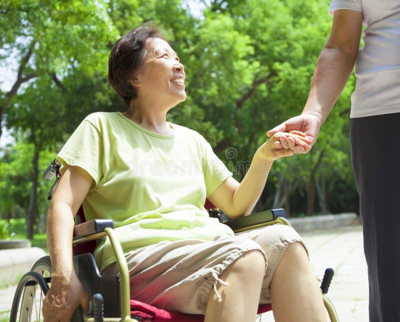 有她的残疾妻子的老人轮椅的 免版税库存图片
