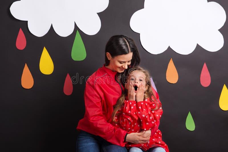 有她的母亲的一个小女孩与云彩和雨珠的黑背景的 免版税库存照片
