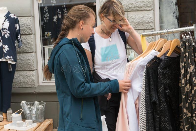 有她的母亲的女孩做看衣裳的购物 免版税库存图片
