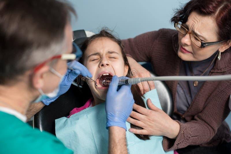 有她的母亲的女孩第一次牙齿参观的 对待耐心女孩牙的资深小儿科牙医 免版税库存图片