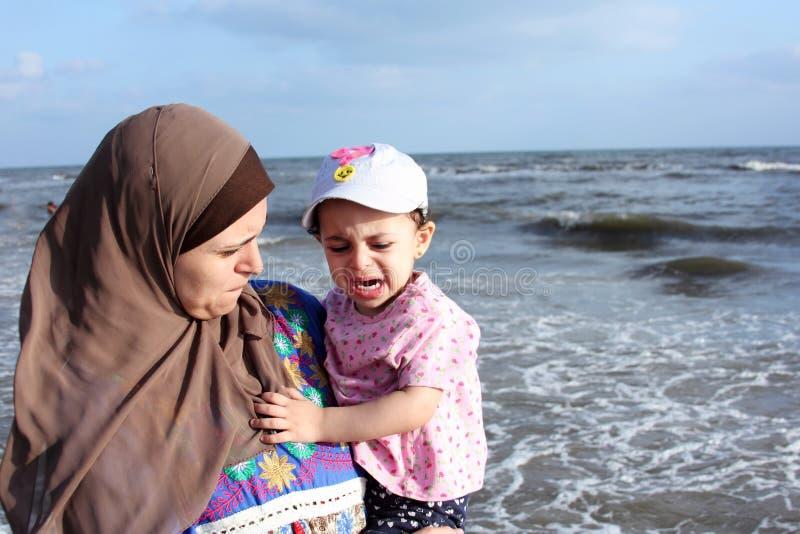 有她的母亲的害怕哭泣的阿拉伯回教女婴 免版税图库摄影