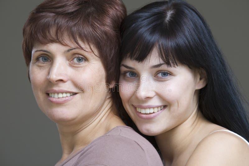 有她的母亲的微笑的少妇 免版税库存照片