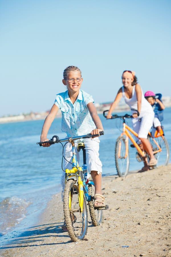 有她的母亲的逗人喜爱的女孩和兄弟乘坐自行车 图库摄影