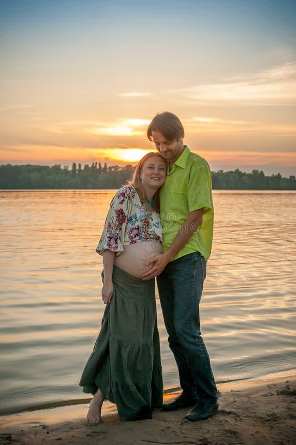 有她的河岸海滩的微笑和接触她的有爱和关心的丈夫的一名怀孕的美丽的妇女腹部 愉快的coupl 免版税库存照片