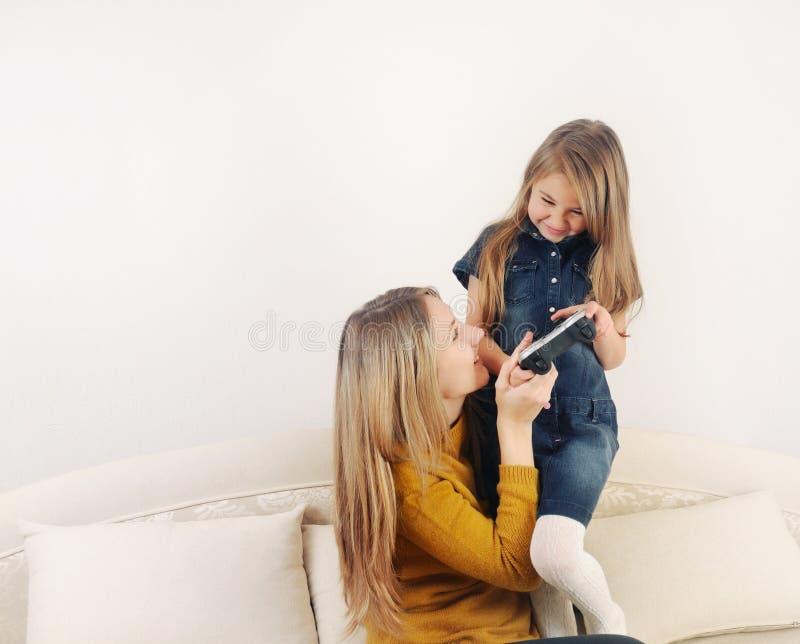 有她的演奏电视在的母亲的小女孩电子游戏设备 免版税库存图片