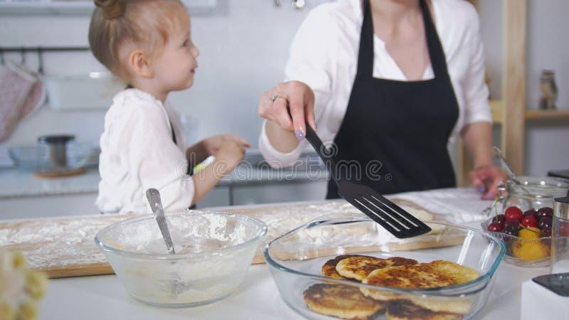 有她的烹调酸奶干酪薄煎饼的小女儿的逗人喜爱的妈妈 免版税图库摄影