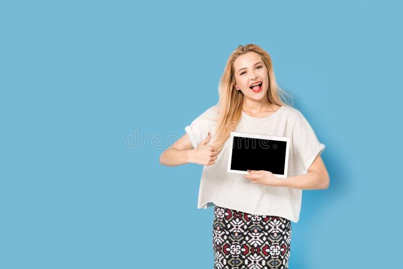 有她的片剂个人计算机的年轻美丽的女孩显示 免版税库存图片