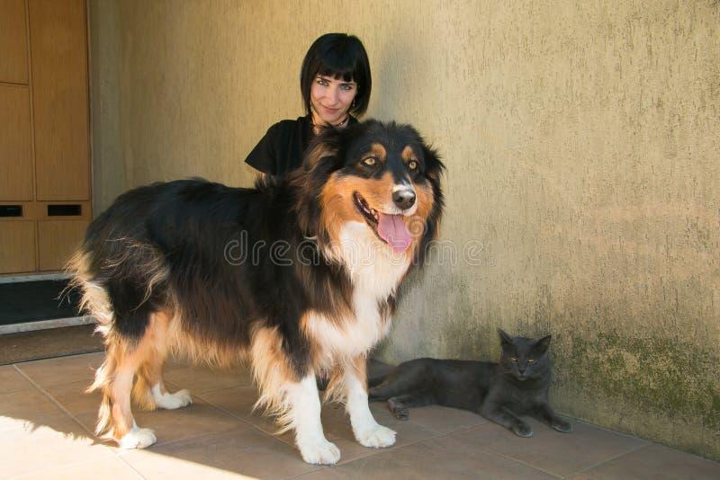 有她的狗和猫的美丽的深色的妇女 免版税库存照片