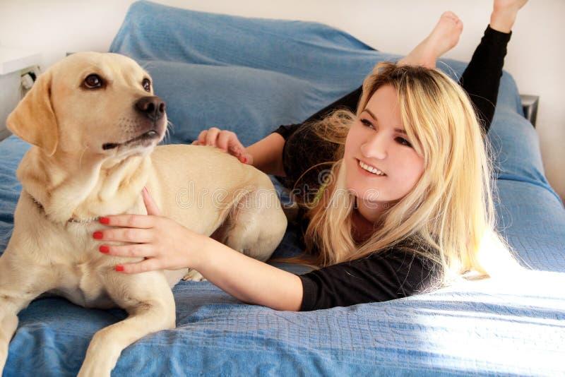 有她的狗的妇女在家床上,放松在卧室 美丽的女孩在床上使用,一起并且宠爱与狗 免版税库存照片