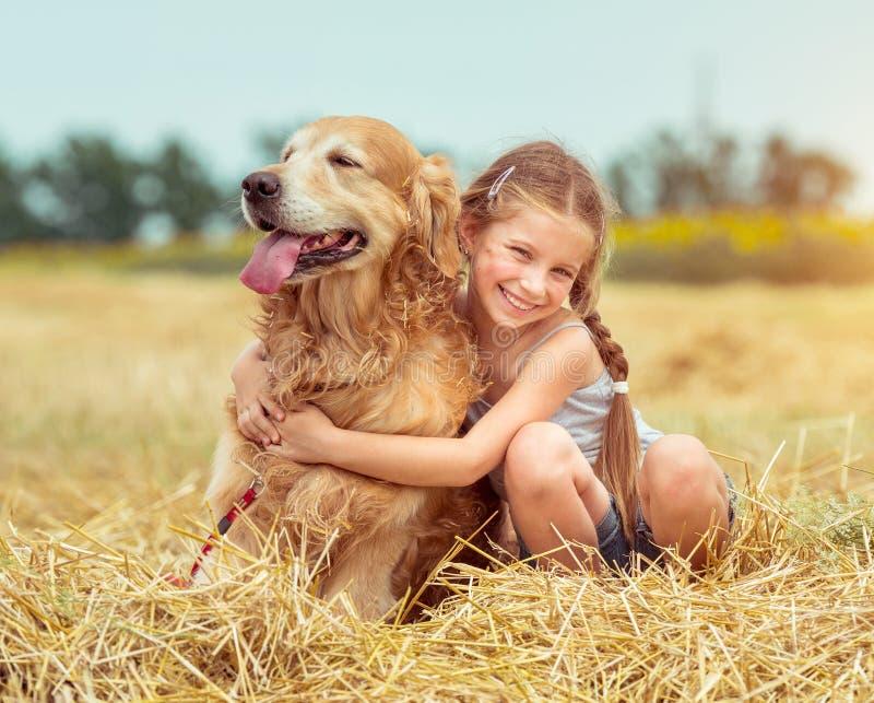 有她的狗的愉快的小女孩 免版税库存图片
