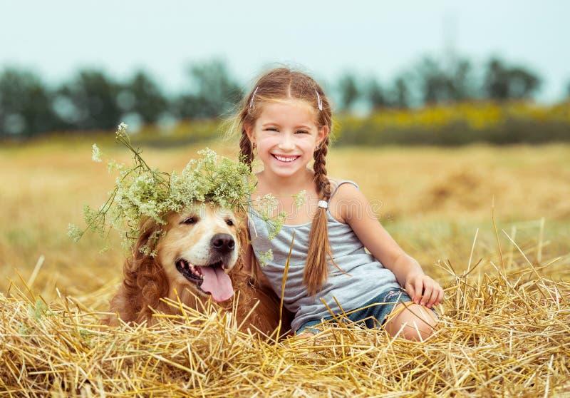 有她的狗的愉快的小女孩 免版税图库摄影