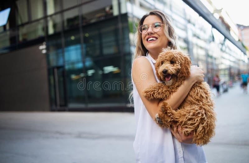 有她的狗的愉快的年轻女人在夏天 图库摄影