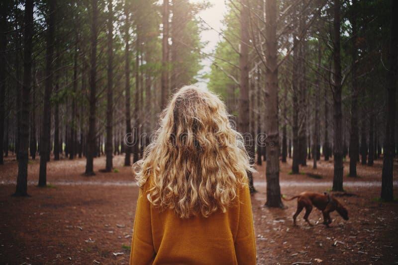 有她的狗的白肤金发的年轻女人在森林里 免版税库存照片