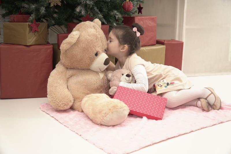 有她的玩具熊朋友的小女孩的圣诞前夕 库存照片