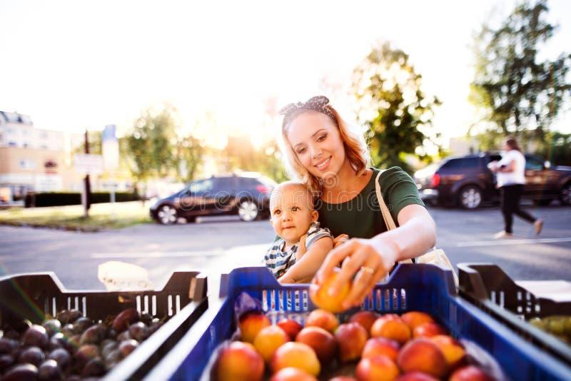 有她的男婴的年轻母亲在室外市场上 免版税库存图片