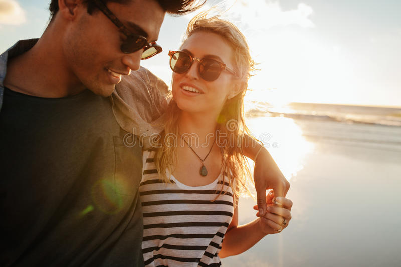 有她的男朋友的美丽的妇女海滩的 库存照片