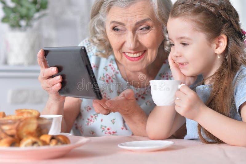 有她的看片剂的祖母的逗人喜爱的女孩 免版税库存照片