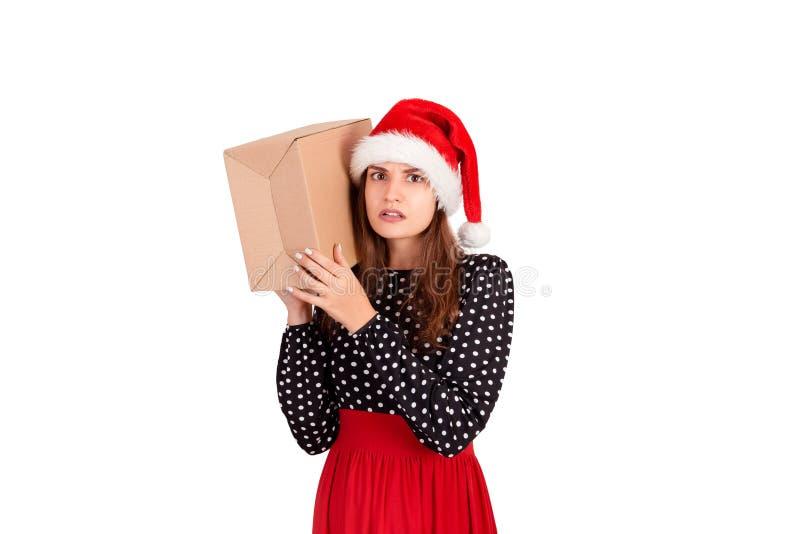 有她的礼物的震惊的女孩听在箱子的什么` s 背景查出的白色 节假日概念 库存图片