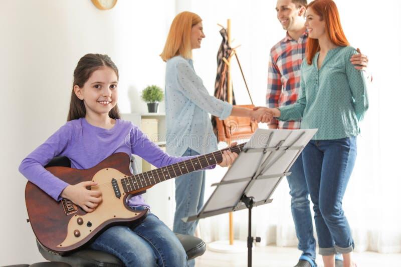 有她的老师和父母的女孩音乐课的 免版税图库摄影