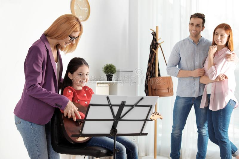 有她的老师和父母的女孩音乐课的 库存图片
