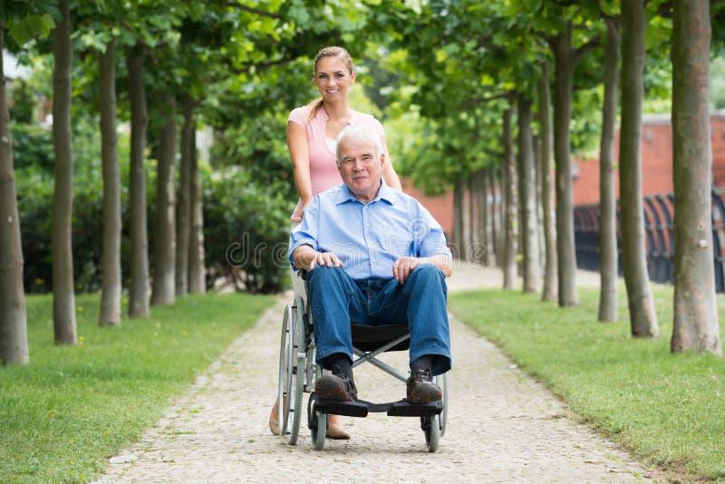 有她的老资深父亲的妇女轮椅的 免版税库存照片