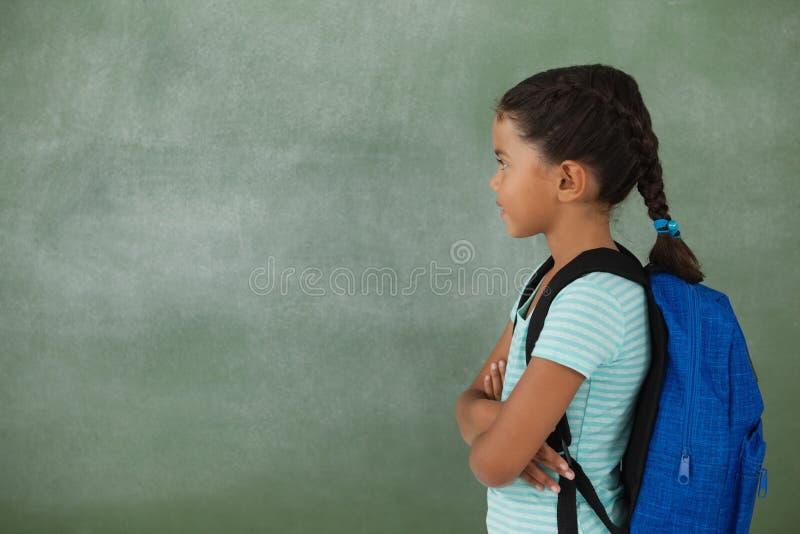有她的胳膊的女孩横渡了反对粉笔板 免版税库存照片