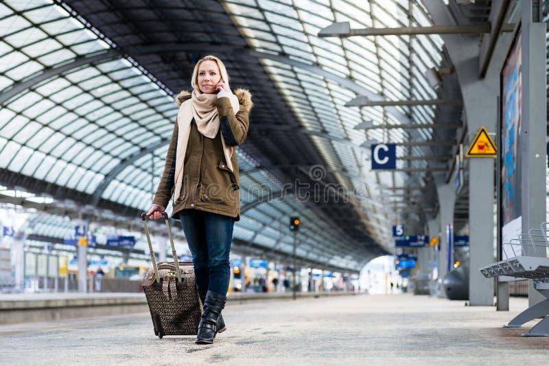 有她的行李的妇女走沿在火车站的平台的 库存照片
