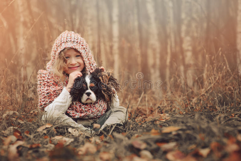 有她的西班牙猎狗狗的愉快的儿童女孩在舒适温暖的秋天步行 免版税库存照片