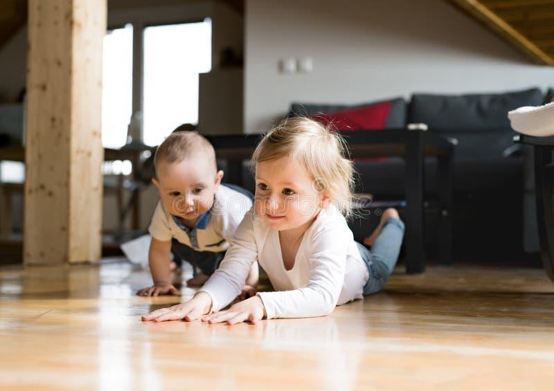 有她的说谎在地板上的小兄弟的逗人喜爱的小女孩 免版税库存图片