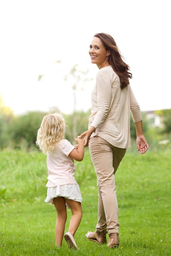 有她的走在公园的女儿的少妇 库存照片