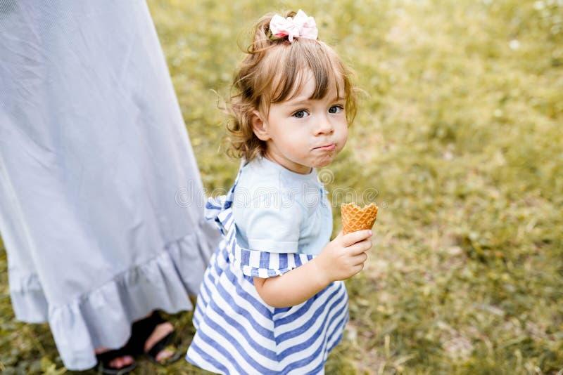 有她的走在公园的女儿的母亲,品尝冰淇凌的女孩 免版税库存图片