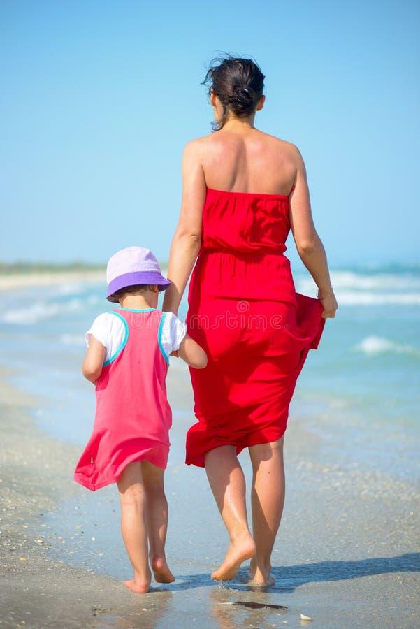 有她的走在海滨的小女孩的母亲 免版税库存图片