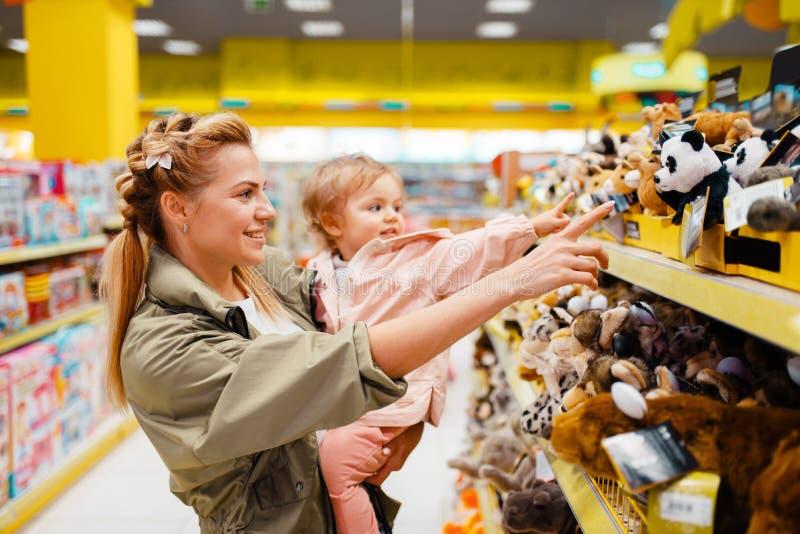 有她的选择玩具的女孩的母亲在孩子商店 库存照片