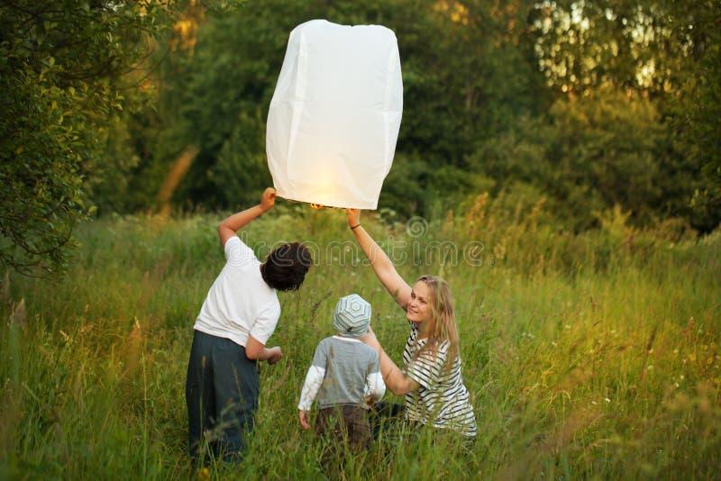 有她的飞行纸灯的儿子的母亲 库存图片