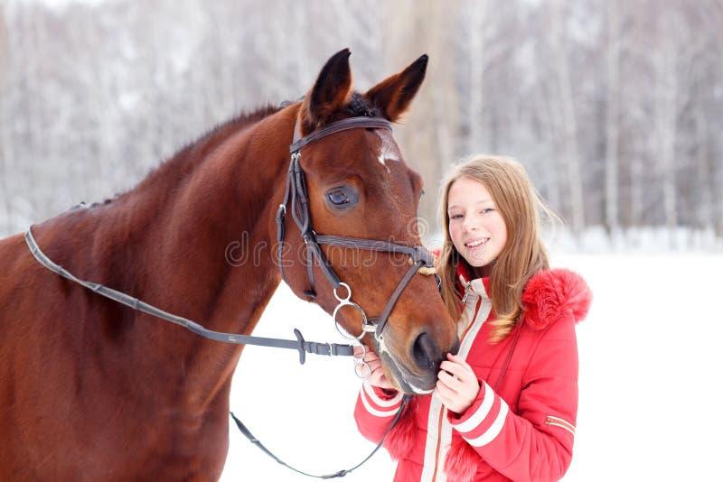 有她的马的年轻十几岁的女孩在冬天公园 库存照片