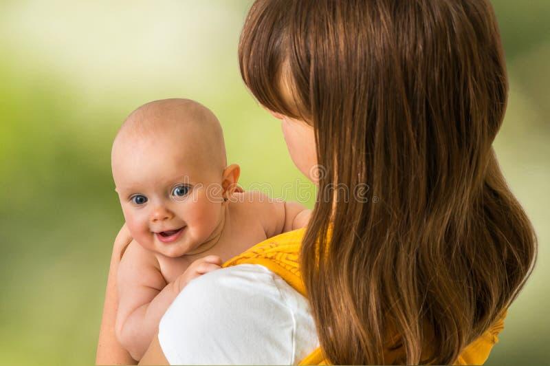 有她的婴孩的愉快的母亲在绿色-隔绝的吊索的 图库摄影