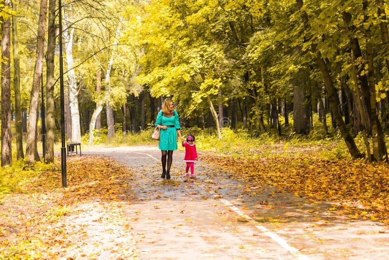 有她的婴孩的母亲 妈妈和女儿在秋天公园 免版税库存图片