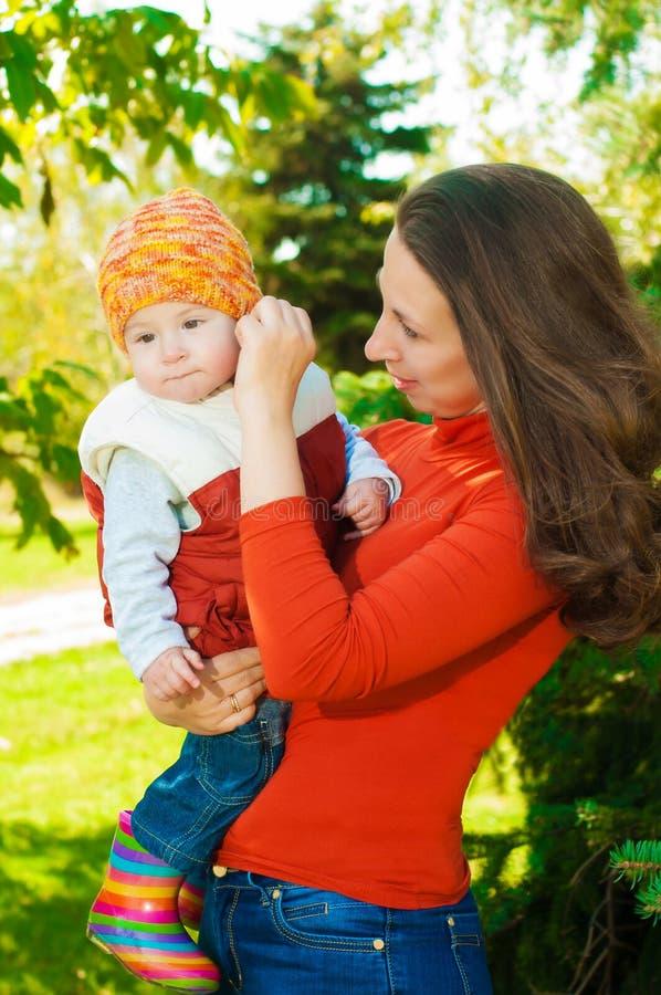 有她的婴孩的年轻母亲在公园 免版税库存图片