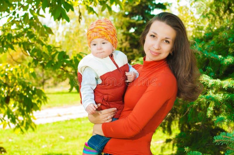 有她的婴孩的年轻母亲在公园 免版税图库摄影