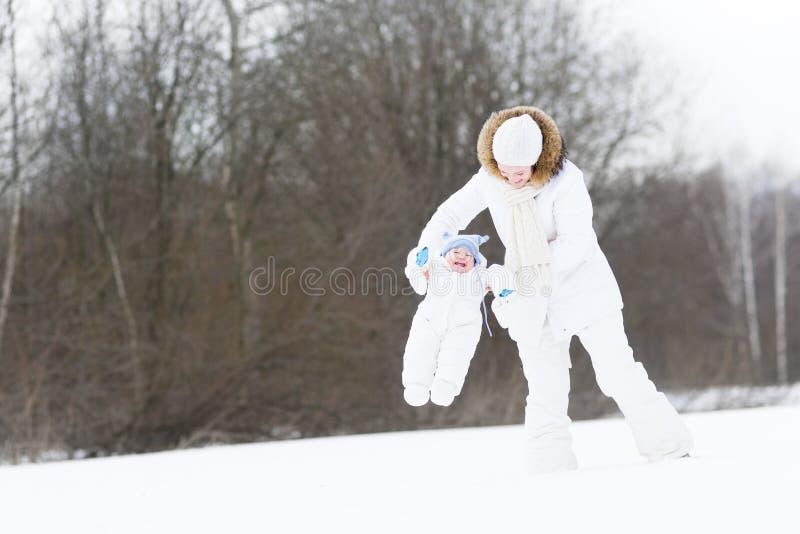 有她的婴孩的年轻母亲在多雪的冬日 图库摄影
